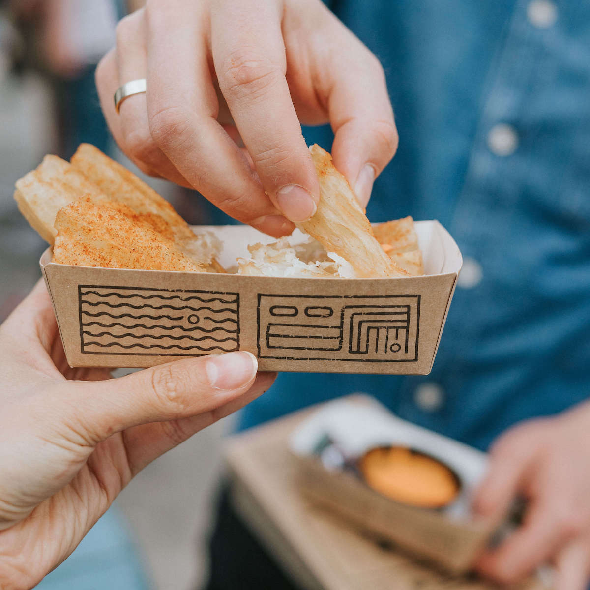 The paper tray with a raised edge perfectly exposes ethnic patterns referring to the style of the streetfood chain Ugood.