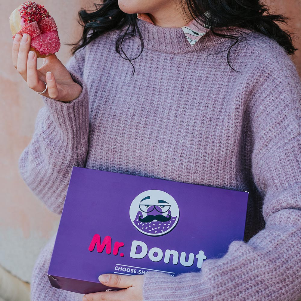 The purple bakery box with the colored logo is a great advertisement for a donut cafe.