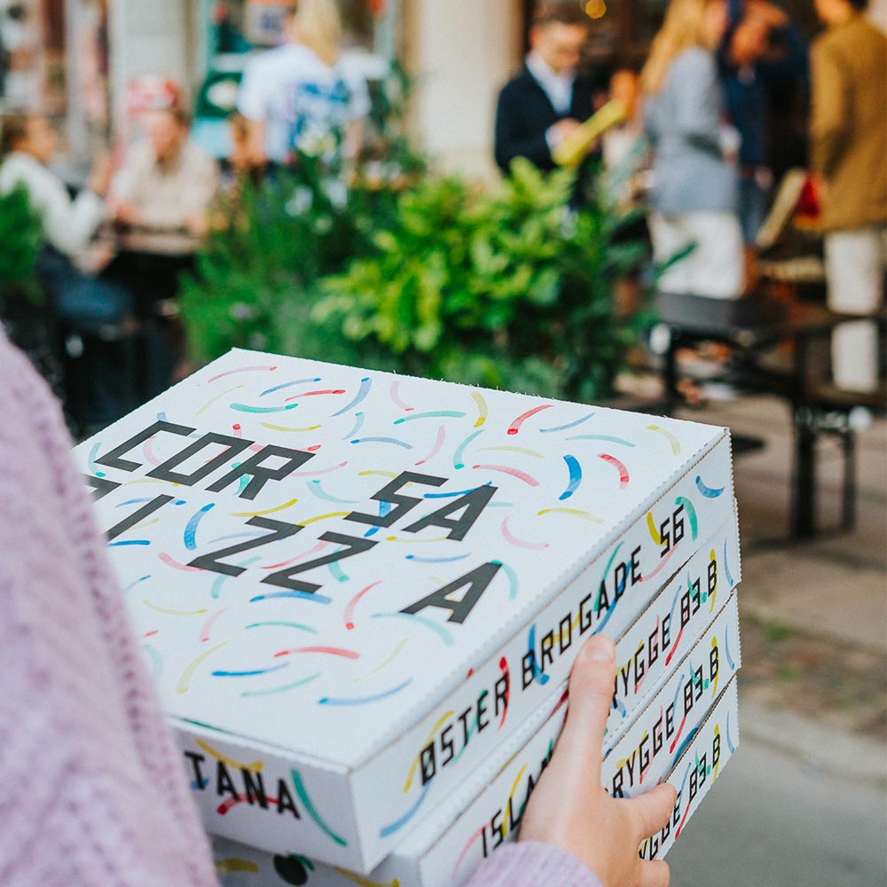 A cardboard pizza box with the Corsa Pizza logo effectively sets the restaurant apart from the competition.