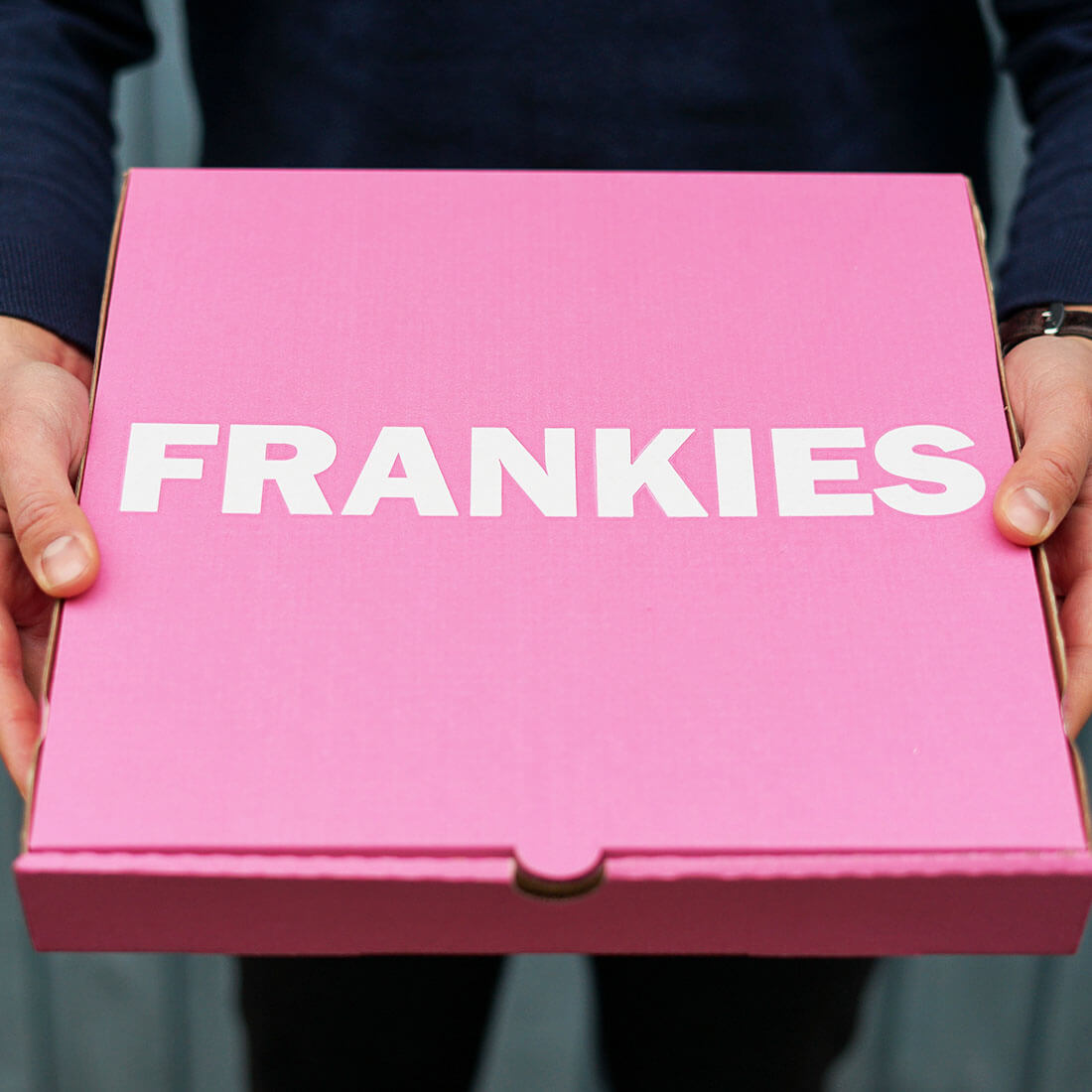 A pink pizza box with a white Frankies logo.
