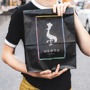 A large black paper bag with the Ugood logo printed on it.