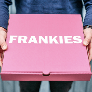 A pink pizza box with the Frankies white logo.