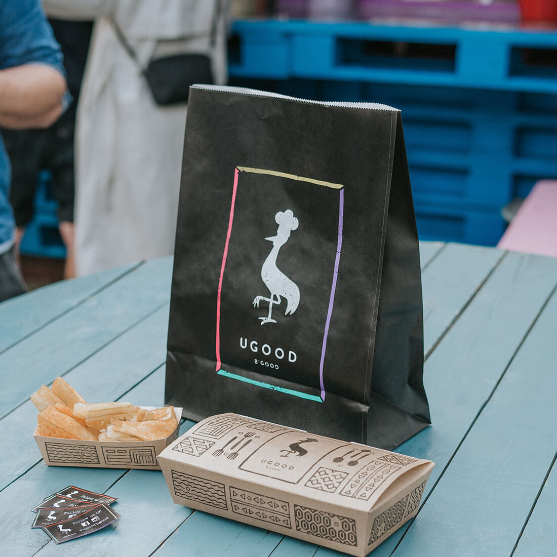 A set of paper packaging made for Ugood street food, characterized by an interesting print and multi-colored print on a paper bag.